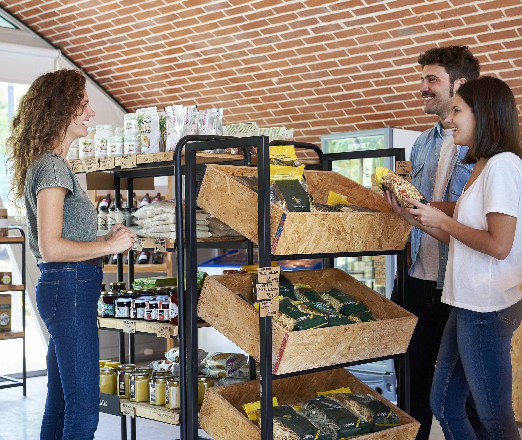 hommes et femmes en magasin bio qui parlent produits Biopartenaire